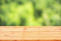 Hölzerne Tischplatte auf bokeh Zusammenfassungs-Grünhintergrund Stockfotografie
