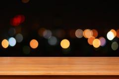 Hölzerne Tischplatte auf buntem bokeh Hintergrund nachts Lizenzfreies Stockfoto