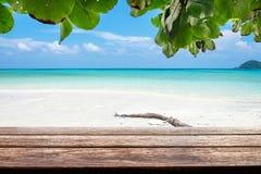Hölzerne Tischplatte auf buntem weißem Sand des Seestrandes Stockfotos