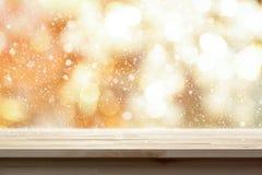 Hölzerne Tischplatte auf glänzendem Gold-bokeh Zusammenfassungshintergrund mit Schnee Lizenzfreie Stockbilder