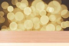 Hölzerne Tischplatte auf goldenem bokeh Zusammenfassungshintergrund Lizenzfreies Stockbild