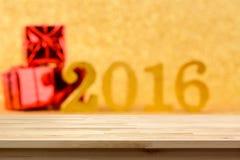 Hölzerne Tischplatte auf goldenem Hintergrund 2016 der Unschärfe Lizenzfreies Stockfoto