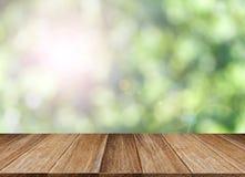 Hölzerne Tischplatte auf grünem bokeh und Blendenfleckhintergrund Lizenzfreie Stockfotos