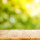 Hölzerne Tischplatte auf grünem bokeh Zusammenfassungshintergrund Lizenzfreie Stockfotos