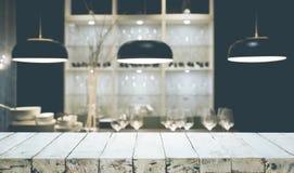 Hölzerne Tischplatte auf heller Zusammenfassung vom Küchenraumhintergrund lizenzfreie stockfotos