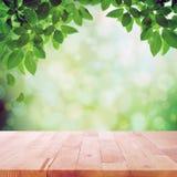 Hölzerne Tischplatte auf Naturgrün bokeh Zusammenfassungshintergrund Stockbilder