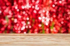 Hölzerne Tischplatte auf rotem bokeh Zusammenfassungshintergrund lizenzfreie stockfotos