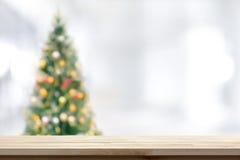Hölzerne Tischplatte auf Unschärfe Weihnachtsbaumhintergrund Stockfotos