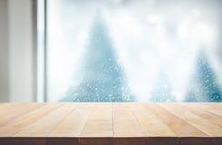 Hölzerne Tischplatte auf Unschärfefensteransicht mit Kiefer in Schneefall O Lizenzfreie Stockfotos