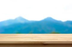 Hölzerne Tischplatte auf Unschärfegebirgshintergrund Lizenzfreie Stockfotos