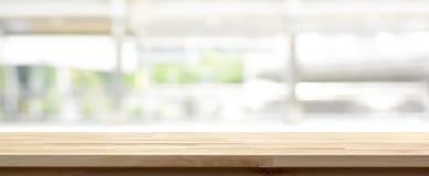 Hölzerne Tischplatte auf Unschärfeküchen-Fensterhintergrund