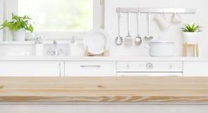 Hölzerne Tischplatte auf Unschärfeküchenraum und Fensterhintergrund stockfoto