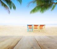 Hölzerne Tischplatte auf Unschärfestrandhintergrund mit Strandstühlen unter Kokosnussbaum Lizenzfreies Stockbild
