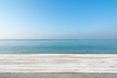 Hölzerne Tischplatte auf unscharfem blauem Meer und weißem Sandstrand backgrou Stockfoto