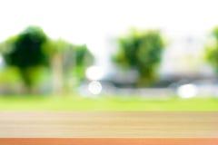 Hölzerne Tischplatte auf unscharfem grünem Naturzusammenfassungshintergrund Stockbild