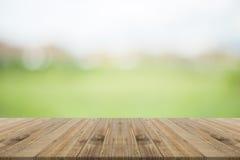 Hölzerne Tischplatte auf unscharfem Hintergrund der Natur Grün Lizenzfreies Stockbild