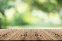 Hölzerne Tischplatte auf unscharfem Hintergrund der Natur Grün Stockfoto
