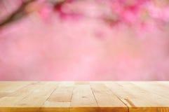 Hölzerne Tischplatte auf unscharfem Hintergrund der rosa Kirschblüte blüht Lizenzfreies Stockfoto