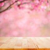 Hölzerne Tischplatte auf unscharfem Hintergrund der rosa Kirschblüte blüht Lizenzfreie Stockbilder
