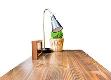 Hölzerne Tischplatte mit Lampe, Bilderrahmen und grünem Busch in der Flechtweide Lizenzfreies Stockbild