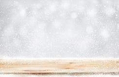 Hölzerne Tischplatte mit Schneefällen des Wintersaisonhintergrundes Weihnachten Lizenzfreies Stockfoto