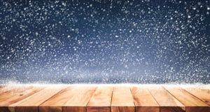 Hölzerne Tischplatte mit Schneefällen des Wintersaisonhintergrundes Weihnachten