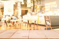 Hölzerne Tischplatte mit Unschärfekaffeestube oder Caférestaurant und Förderung unterzeichnen, abstrakter bokeh Licht-Bildhinterg stockbild