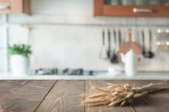 Hölzerne Tischplatte mit Weizen auf Unschärfeküchen-Raumhintergrund für Montageprodukt stockfotografie