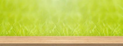 Hölzerne Tischplatte und grünes Gras für Produkt- und Anzeigenmontagefahnengröße verwischen stockfotos
