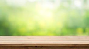 Hölzerne Tischplatte und Unschärfe des neuen grünen bokeh vom Gartenhintergrund stockfotografie