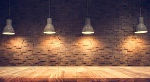 Hölzerne Tischplatte an verwischt vom Gegencaféshop mit Glühlampe stockfotografie