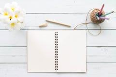 Hölzerne Tischplattentabelle des modernen weißen Büros mit Notizbuch, Notizblock a Lizenzfreie Stockfotos