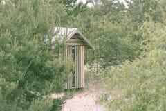 Hölzerne Toilette am sandigen Strand an einem regnerischen Tag im wolkigen Wetter Lizenzfreies Stockfoto