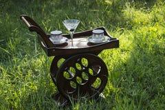 Hölzerne Tray With Wheels And Coffee-Schalen und Martini-Glas in der Natur Stockfotos
