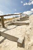 Hölzerne Treppe auf Sand zum blauen Himmel lizenzfreie stockfotos