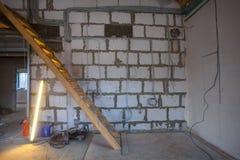 Hölzerne Treppe, leuchtende Rohrlampe und -materialien für Reparaturen und Werkzeuge im Wohnungsbau, der unter der Umgestaltung i stockbilder