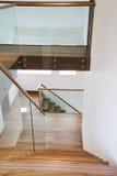 Hölzerne Treppe und Glasgeländerdocken Stockbild