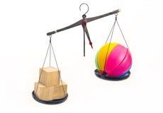 Hölzerne und Plastikspielwaren wogen symbolisch auf den Skalen Lizenzfreie Stockbilder