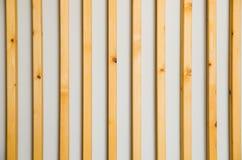 Hölzerne vertikale Latten batten auf einem hellgrauen Wandhintergrund Innendetail, Beschaffenheit, Hintergrund Das Konzept des Mi stockfoto