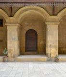 Hölzerne verzierte Tür gestaltet durch gewölbte Ziegelsteinsteinwand lizenzfreie stockbilder