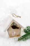 Hölzerne Vogelhaus-Weihnachtsdekoration auf Schneehintergrund Stockfotos