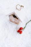 Hölzerne Vogelhaus-Weihnachtsdekoration auf weißem Schneehintergrund Lizenzfreie Stockfotografie