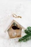 Hölzerne Vogelhaus-Weihnachtsdekoration auf weißem Schneehintergrund Lizenzfreies Stockfoto
