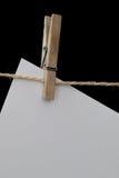 Hölzerne Wäscheklammer, die Weißbuch auf einem Draht hält Lizenzfreie Stockfotos