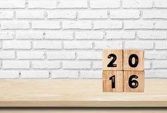 Hölzerne Würfel mit 2016 auf Holztischhintergrund Stockfotos