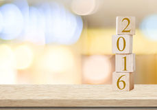 Hölzerne Würfel mit 2016 auf Tabelle über Unschärfehintergrund, neues Jahr t Stockfotografie