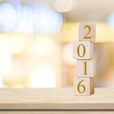 Hölzerne Würfel mit 2016 auf Tabelle über Unschärfehintergrund, neues Jahr t Stockfotos