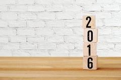 Hölzerne Würfel mit 2016 auf Tabelle, Hintergrundschablone des neuen Jahres Lizenzfreies Stockfoto
