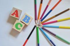 Hölzerne Würfel mit den Buchstaben des englischen Alphabetes Nahe bei ihnen sind farbige Bleistifte Beschneidungspfad eingeschlos Lizenzfreie Stockfotografie