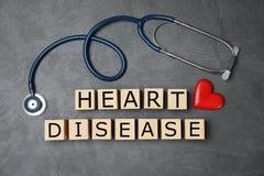 Hölzerne Würfel mit Text Herz-Krankheit und Stethoskop auf grauem Hintergrund stockfotografie